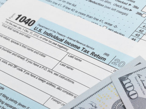US Tax Form 1040 with 100 dollars bills - 1 to 1 ratio